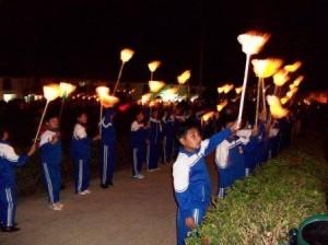Los  niños llevan una vela como símbolo de paz